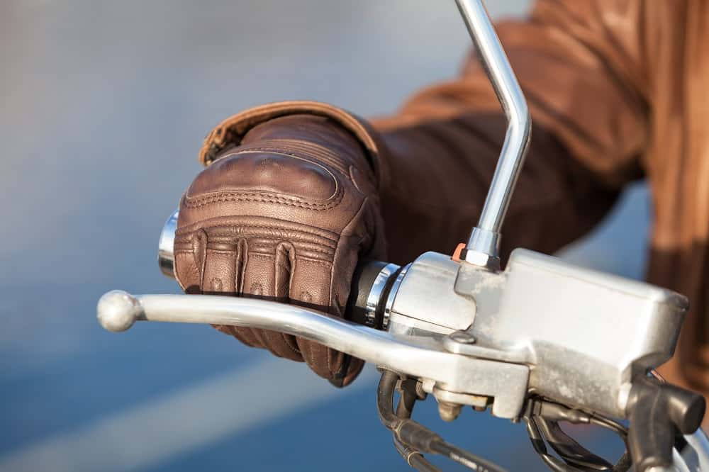 Motorcyclist arm in brown leather glove