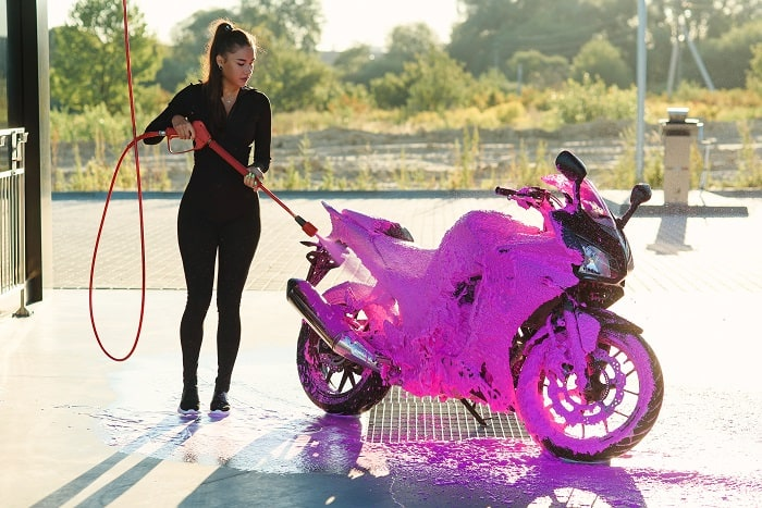 Beautiful girl washes a motorcycle